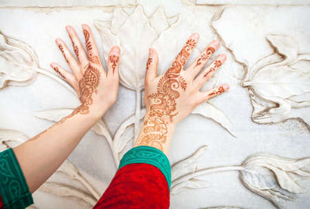 henna: Woman in red Indian costume touching white marble wall with floral pattern by hands in henna painting in Taj Mahal in Agra, Uttar Pradesh, India Stock Photo