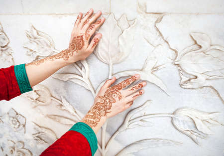 marble wall: Woman in red Indian costume touching white marble wall with floral pattern by hands in henna painting in Taj Mahal in Agra, Uttar Pradesh, India Stock Photo