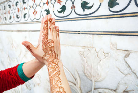 namaste: Woman in red Indian costume ding Namaste gesture by hand in henna paintings  near the marble wall with floral pattern in Taj Mahal in Agra, Uttar Pradesh, India