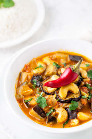 veggies: Eggplant curry with cashew nuts served with red chili on the top and basmati rice on white background Stock Photo