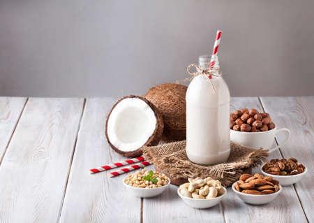 alimentos y bebidas: leche vegana de los frutos secos en la botella con rojo despojado de paja alrededor de varias tuercas en mesa de madera blanca Foto de archivo