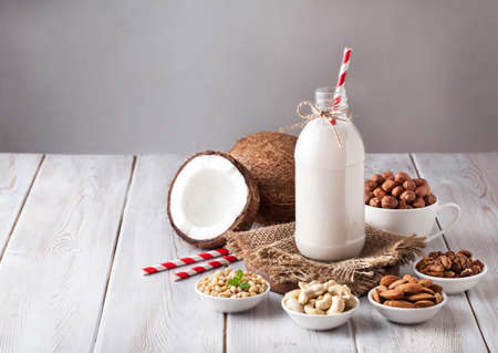 cashew: Vegan milk from nuts in the bottle with red stripped straw around various nuts on white wooden table