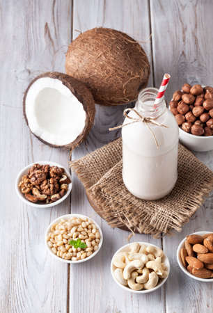 Vegan milk from nuts in the bottle with red stripped straw around various nuts on white wooden table