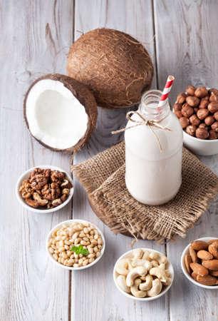 Vegan melk van noten in de fles met rode gestripte stro rond verschillende noten op witte houten tafel Stockfoto - 50396493