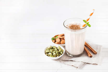 stick of cinnamon: Indian almond lassi curd with spices cardamom and cinnamon in the glass with striped stick on white background with space for text