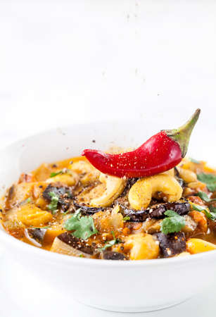 veggies: Eggplant curry with cashew nuts, chili and coriander on white background with space for text Stock Photo