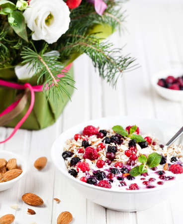 winter flower: Bowl with oats, berries and almond near winter flower bouquet on wooden white background