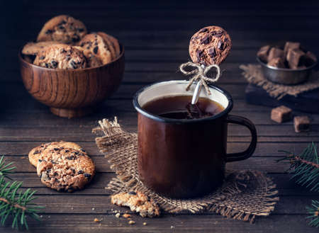 christmas meal: Decorative spoon from polymer clay in the mug with tea near chocolate cookies on wooden background