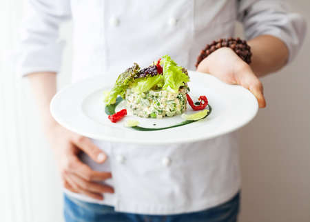 Chef holding Healthy Raw vegan salad in the white plate in restaurant