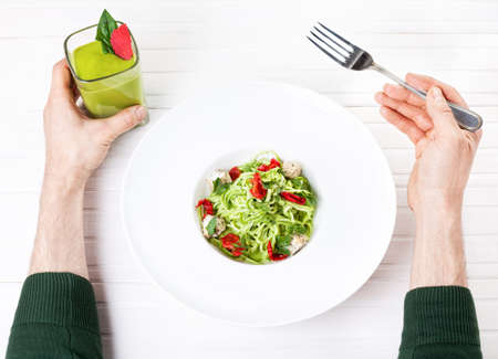 veggies: Man holding green smoothie and eating Raw vegan spaghetti from zucchini, sun dried tomatoes and nut cheese on white background in restaurant