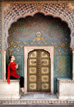 padma: Woman in red scarf sitting near Lotus gate in City Palace of Jaipur, Rajasthan, India