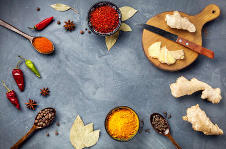 Various Spices powder turmeric, chili, bayberry, bay leaf, ginger on cutting board, cinnamon, cumin, star anise on grey stone background with space for your text, shot from aerial view close-up