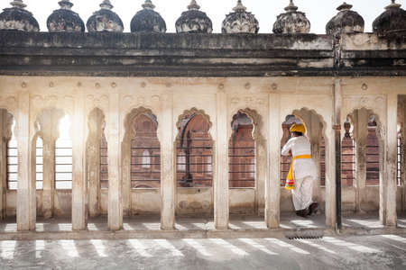 balcony window: JODHPUR, RAJASTHAN, INDIA - MARCH 08, 2015: Man in traditional Rajasthan cloth loking from balcony window in Mehrangarh fort palace