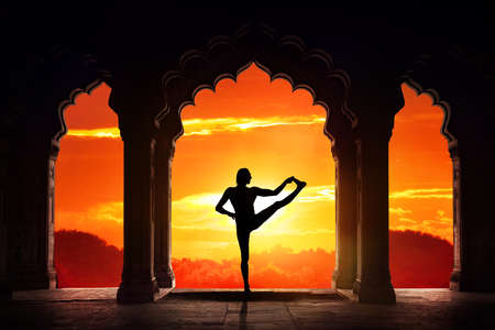 arch: Man silhouette doing yoga advance balance asana in old temple at orange sunset sky background