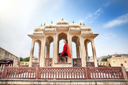 windy city: Woman in red dress with scarf sitting on the decorative Royal balcony in Hawa Mahal, Rajasthan, India