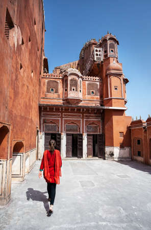 windy city: Woman in red dress with scarf going to enter Hawa Mahal, Rajasthan, India Stock Photo