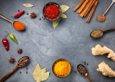 Various Spices powder turmeric, chili, bayberry, bay leaf, ginger, cinnamon, cumin, star anise on grey stone background with space for your text, shot from aerial view close-up
