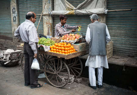 AGRA, UTTAR PRADESH, INDIA - FEBUARY 24, 2015: Muslim man buying fruits from the seller on the Taj Ganj Street