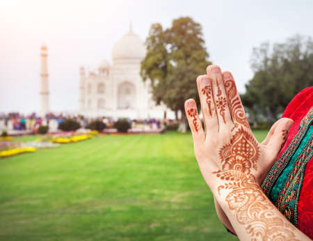 Woman hands with henna painting in Namaste gesture near Taj Mahal in Agra, Uttar Pradesh, India Banco de Imagens