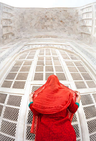 agra: Woman in red costume standing near marble gate and looking at Taj Mahal in Agra, Uttar Pradesh, India