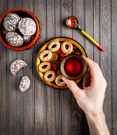 bublik: Table with Russian dessert sweet gingerbread and holding bublik biscuit, wooden spoon painted with floral ornament in the style of Khokhloma at wooden table. Concept of Russian traditional food. Stock Photo
