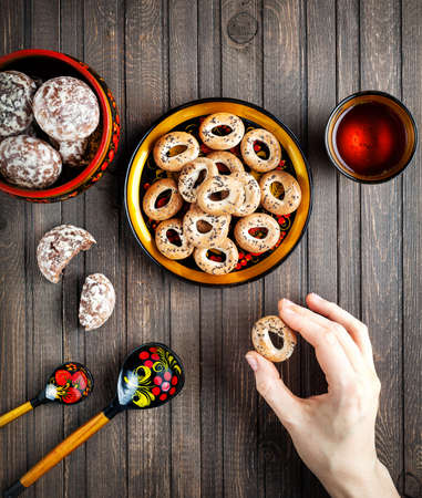 bublik: Table with Russian dessert sweet gingerbread and woman hand holding bublik biscuit, wooden spoon painted with floral ornament in the style of Khokhloma at wooden table. Concept of Russian traditional food. Stock Photo