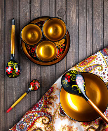 russian: Wooden dishes, painted with floral ornament in the style of Khokhloma Russian wood art on the table with shawl.