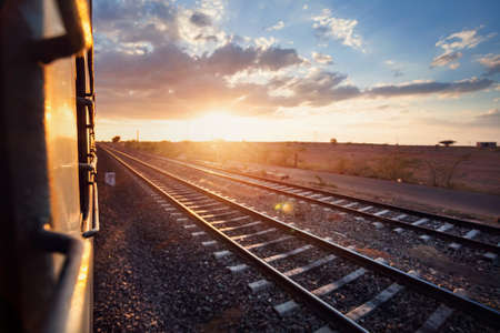 train station: Train passing desert area at sunset sky beckgroung in Rajasthan, India Stock Photo