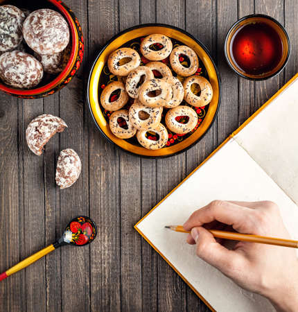 bublik: Table with Russian dessert sweet gingerbread and bublik biscuits, wooden spoon painted with floral ornament in the style of Khokhloma at wooden table. Concept of Russian traditional food. Stock Photo