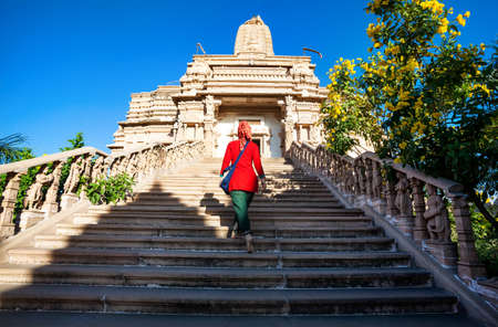 maharashtra: Indian woman in red dress on the stairs of Jain temple in Nasik, Maharashtra, India