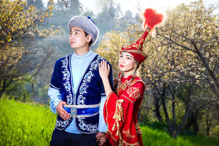 kazakh: Couple in Kazakh ethnic costume in Spring Blooming apple garden of Almaty, Kazakhstan, Central Asia