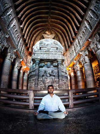 Indian Man doing meditation in lotus pose near the statue in ancient Ajanta cave near Aurangabad, Maharashtra, India photo