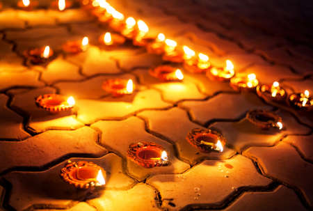 diyas: Traditional clay diya lamps lit on the ground during festival diwali celebration
