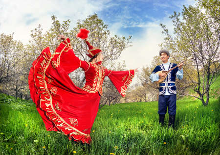 Kazakh woman dancing in red dress and man playing dombra at Spring Blooming garden in Almaty, Kazakhstan, Central Asia Reklamní fotografie - 53190866