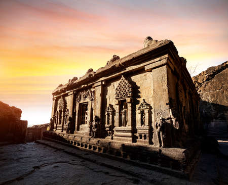 夕暮れ時のマハラシュトラ州、インド アウランガーバード近郊のエローラ石窟の廃墟で切り分けられた彫像 写真素材