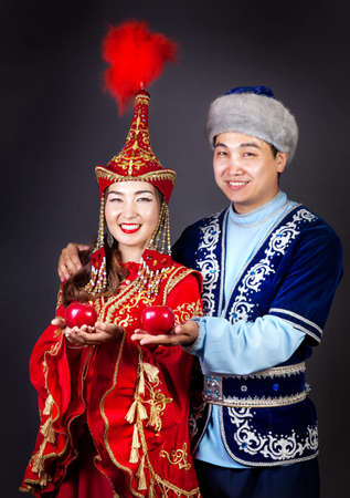 Asian couple in national Kazakh costumes holding red apples at grey background