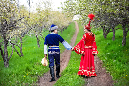 tribal park: Couple in Kazakh costume walking around Spring Blooming apple garden of Almaty, Kazakhstan, Central Asia