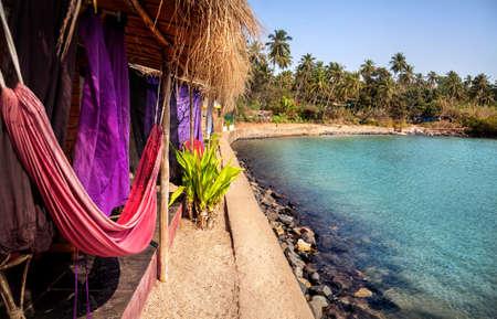 india fisherman: Resort with hammock near lagoon in sunny day at tropical Palolem beach in Goa, India