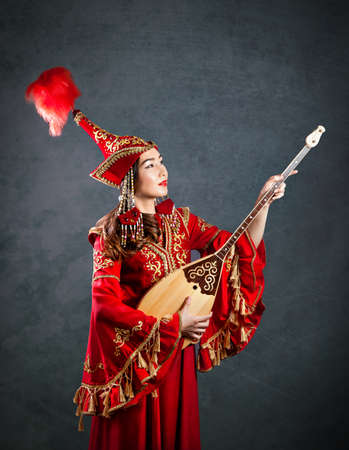 kazakh: Kazakh woman in red costume playing dombra Kazakh musical instrument at the grey background Stock Photo