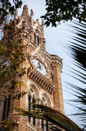 university: Rajabai Clock Tower at blue cloudy sky background in Mumbai, India Stock Photo