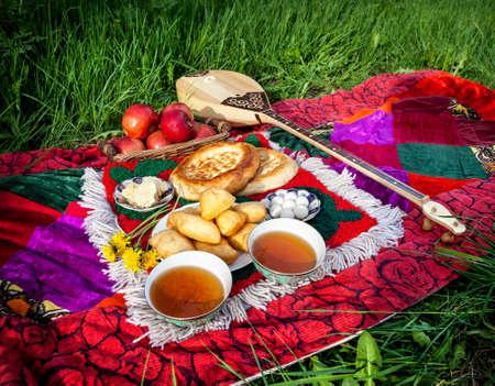 cuisine entertainment: Two cups of black tea, Dombra Kazakh instrument, apples and baursak dish at picnic in Kazakhstan