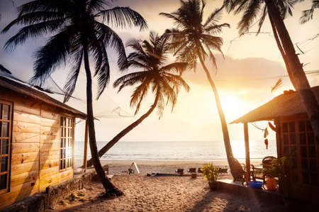 fiji: Wooden cottage with sea view in tropical resort with curved coconut palm trees and sunbed on the beach at beautiful sunset Stock Photo