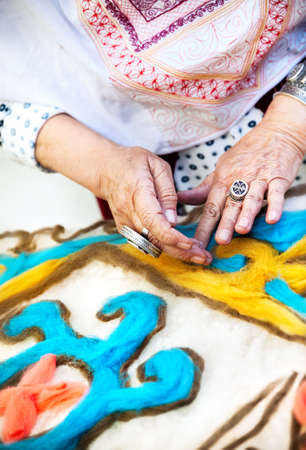 nomad: Ethnic woman making pattern on the Kazakh blanket in the market at Nauryz celebration in Almaty, Kazakhstan Stock Photo
