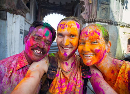 Udaipur, India - March 6, 2015: Selfie photo of Indian man and foreign couple with painted face celebrating the colorful festival of Holi on the street.