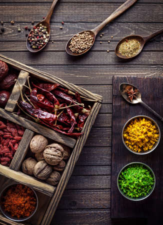 Spices, dry fruits and walnuts in the wooden box at wooden background with spoons nearby