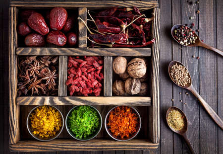 curry powder: Spices, dry fruits and walnuts in the wooden box Stock Photo