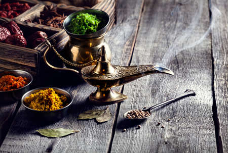 black magic: Aladdin Lamp from bronze and dry spices at wooden background with spoons nearby Stock Photo