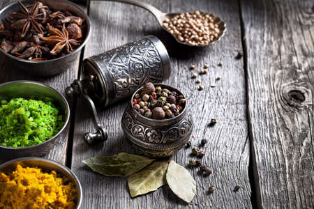 spice market: Spices, bronze pepper grinder and spoon with cumin seeds at wooden green background