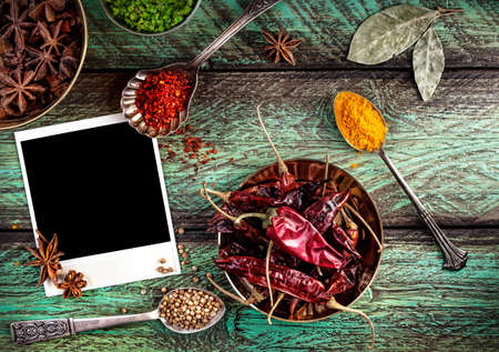 red pepper: Spices, blank photo frame and dry red chili peppers at wooden green background with spoons nearby