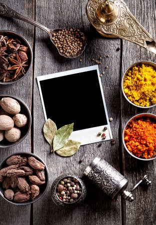 Spices, pepper grinder, blank photo frame and dry red chili peppers at wooden green background with spoons nearby Foto de archivo
